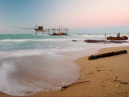 Beautiful view of trabocco with the waves on the golden sand