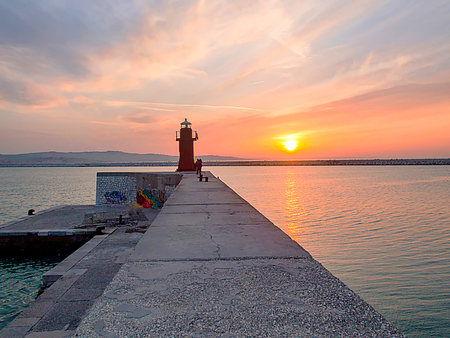 The lantern. Red lighthouse in Anconas tourist and historic harbor with sky overcast with stunning clouds and a beautiful sunset in the background reflecting on the crisp blue sea water Stock Photo