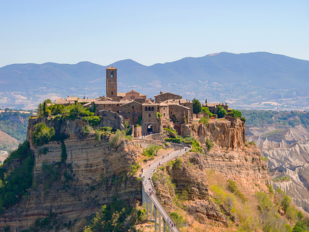 view of the beautiful Civita di Bagnoregio, Italy, with the famous bridge below and the mountains in the background