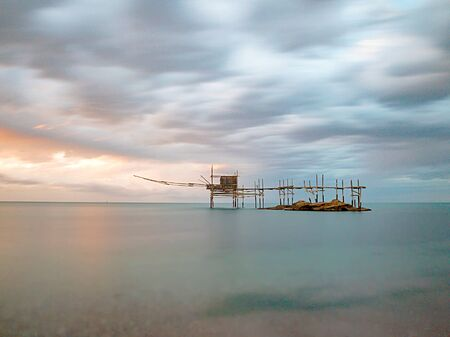 Drifting Trabocco (or Trabucco) isolated in the sea, with the sun's rays at sunset reflecting on the blue water and clouds running fast in the sky