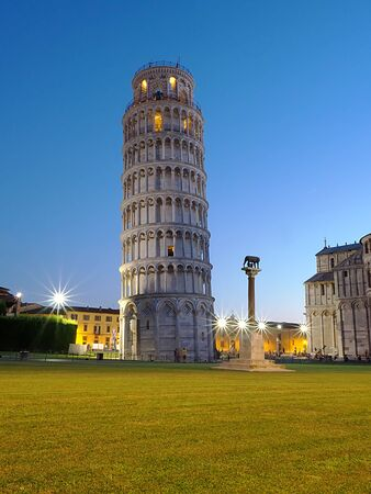 characteristic tower of Pisa (inclined) at night illuminated by lampposts and with a blue sky