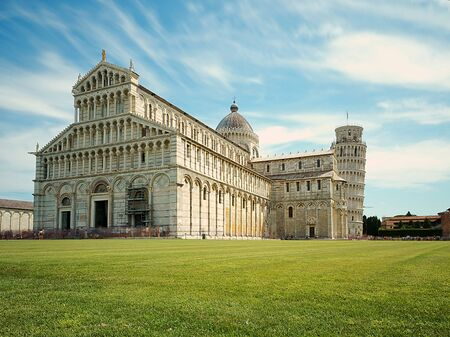 pisa cathedral and pisa tower, with the green lawn at the base and fantastic concentric clouds in the sky