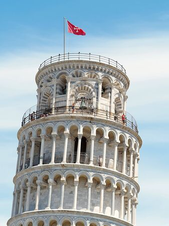 Tower of Pisa close up. macro detail upper part of the characteristic tower of Pisa (inclined) showing the red flag showing its vertical inclination, with clouds in the background