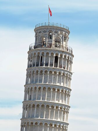 upper part of the characteristic tower of Pisa (inclined) with the red flag showing its vertical inclination, with clouds in the background 版權商用圖片