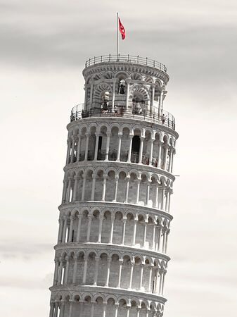 upper part of the characteristic tower of Pisa (inclined) in black and white with the red flag showing its vertical inclination, with clouds in the background