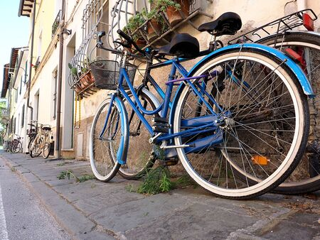blue bicycle leaning against the wall of an Italian house