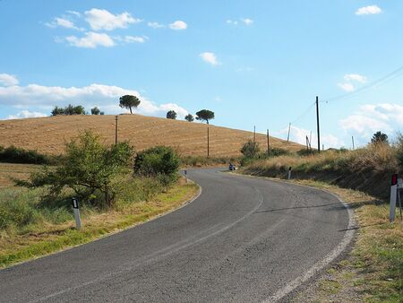 Tuscany, paved road that crosses and curves between the Crete Senesi landscape.