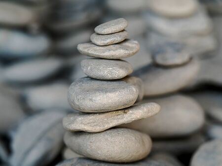 small zen stones on each other in perfect balance and harmony, with other stone sculptures in the background Zdjęcie Seryjne