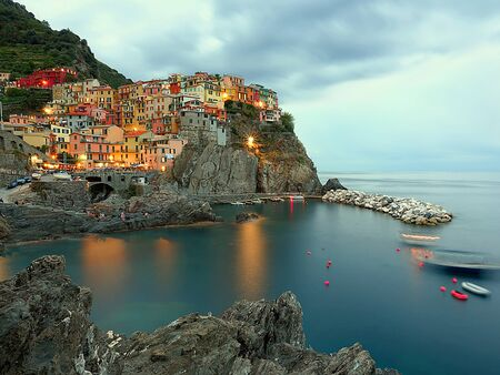 Manarola in the evening, a characteristic city of the Cinque Terre (Italy), with colorful houses on a cliff by the sea, lit by lampposts and by the light of the sunset with a cloud in the sky Фото со стока