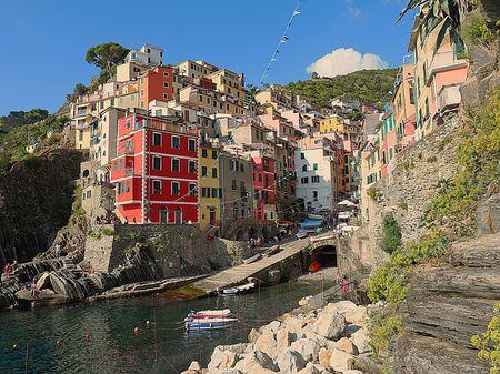View of the town of Riomaggiore, a characteristic town of the Cinque Terre (Italy), with colorful red and yellow houses on a cliff overlooking the sea, with a blue sky