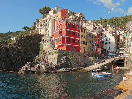 View from the cliff over the sea of Riomaggiore, characteristic city of the Cinque Terre (Italy), with colorful red and yellow houses on the sea and the colors reflected in the water