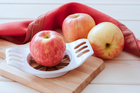 slicer: Apples and slicer on a wood background. Stock Photo