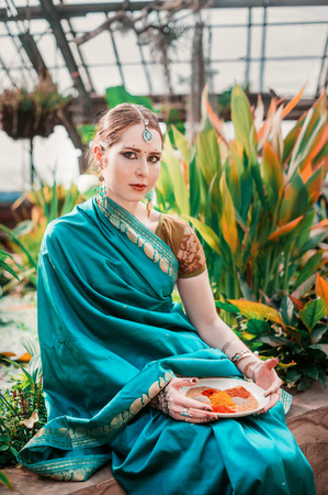 mehandi: The european girl in the blue Indian costume.