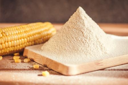harina: harina de maíz y el maíz en la mazorca en una mesa de madera