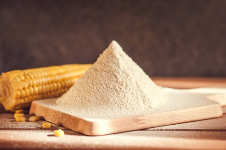 mais: corn flour and corn on the cob on a wooden table Stock Photo