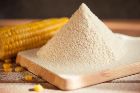 elote: harina de maíz y el maíz en la mazorca en una mesa de madera