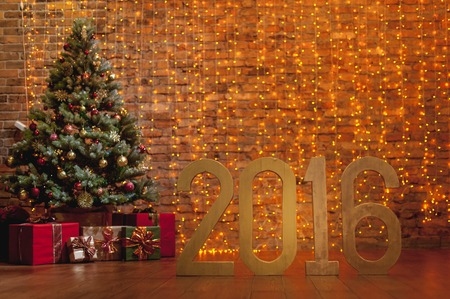 brick wall: Letters 2016 and decorated Christmas tree on brick wall background