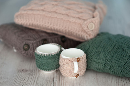 throw cushion: three knitted pillows and two cups  on wooden board background.