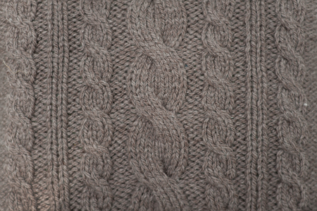 cable stitch: A handmade grey knitting wool texture background.