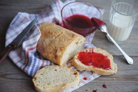 strawberry jam sandwich: Bread with homemade jam in plate on wooden table, closeup. Stock Photo