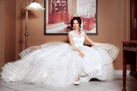 luxury hotel room: Beautiful bride in in the lush dress luxury hotel room.