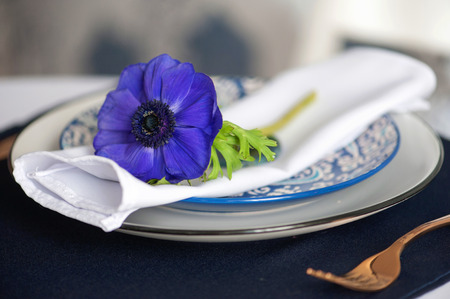 Wedding table setting with blue anemones and iris. Stock Photo