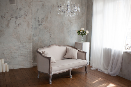 natural light: wedding decoElegant sofa with floral decor. Luxury interior in white colorsr interior style
