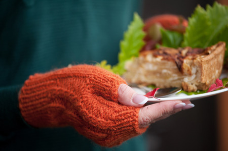 Hands in orange mittens hold a plate with a cake. Stock Photo