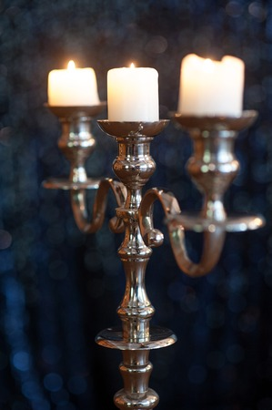 silver candlestick with three burning white candles in front of dark background.
