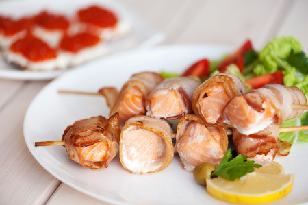 Roasted salmon meat pieces wrapped in bacon slices.