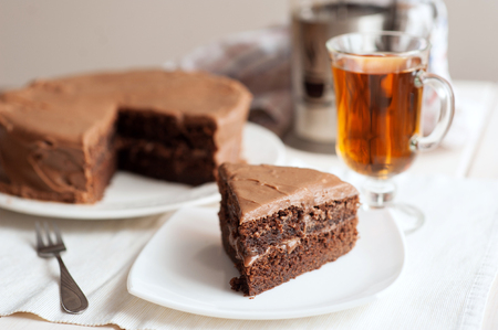 Chocolate cake with a cut piece and cup of tea. Stock Photo