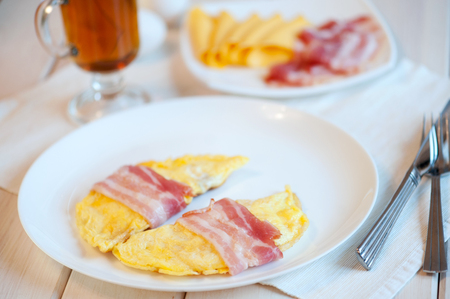Delicious omelette on a plate. Omelette wrapped in bacon. Stock Photo