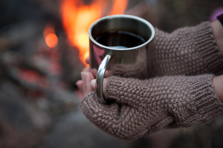 tea hot drink: Hands in mitts holding hot tea cup outdoor near bonfire.