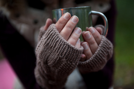 Metal mug with hot tea in a hands in a warm cozy mittens. Stock Photo