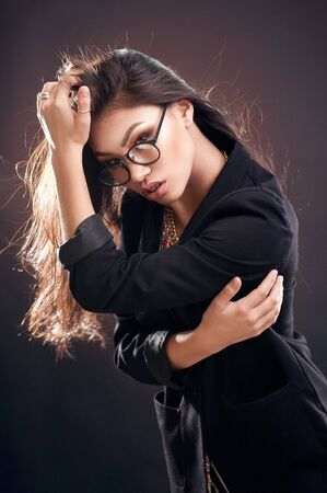 Portrait of a beautiful girl in round glasses on a brown background in the studio
