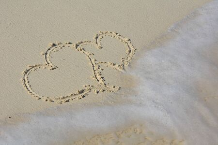 Hearts wrote in the sand and washed away by waves.