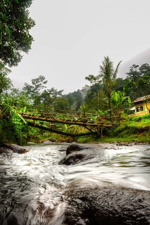 Tropical landscape with rocky river under the wooden bridge and typical rural Indonesian house in the Jungle of west Java