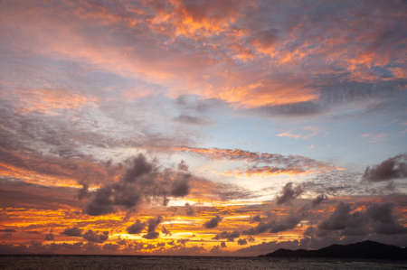 Beautiful tropical sunset over the sea horizon with black silhouette of an island. Seychelles