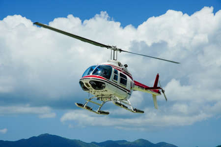 Helicopter on scenic flight with clouds and blue sky in a tropical place