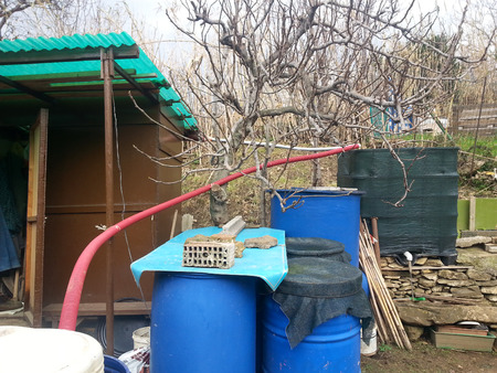 behind the scenes: Behind the scenes of a vegetable garden where the gardener collects water and keeps tools Stock Photo