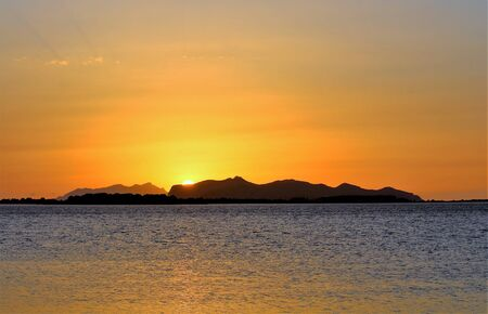 evocative image of the sunset over the sea with a promontory in the background in Sicily Archivio Fotografico - 127172093