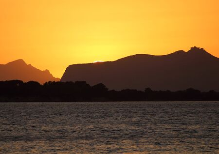 evocative image of the sunset over the sea with a promontory in the background in Sicily Archivio Fotografico - 127172099