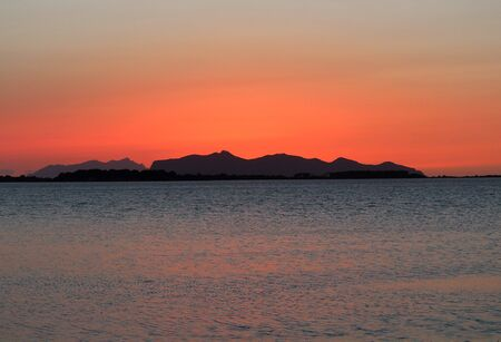 evocative image of the sunset over the sea with a promontory in the background in Sicily Archivio Fotografico - 127174223