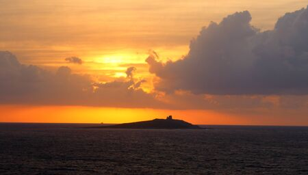 evocative image of sunset over the sea with island in the background Archivio Fotografico - 127174469