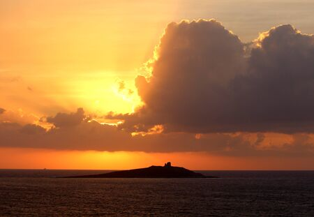 evocative image of sunset over the sea with island in the background Archivio Fotografico - 127174471