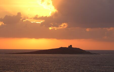evocative image of sunset over the sea with island in the background Archivio Fotografico - 127174472