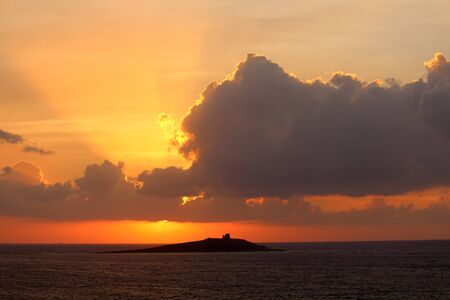 evocative image of sunset over the sea with island in the background Archivio Fotografico - 127174473