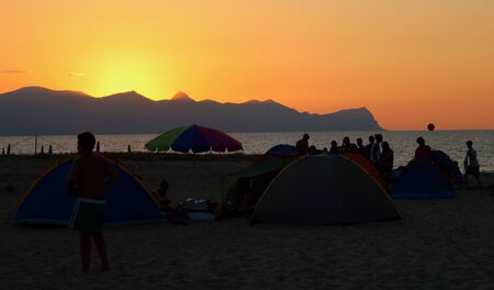 evocative image of sunset over the sea, silhouette of tents and people camping on the beach Archivio Fotografico - 127174475