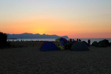 evocative image of sunset over the sea, silhouette of tents and people camping on the beach Archivio Fotografico - 127174476