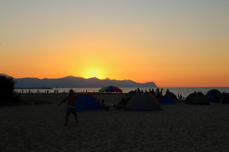 evocative image of sunset over the sea, silhouette of tents and people camping on the beach Archivio Fotografico - 127175610